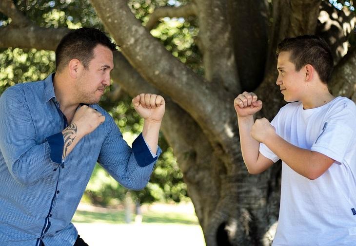 כללים להורות יעילה: אב ובן עומדים זה מול זה עם אגרופים קפוצים