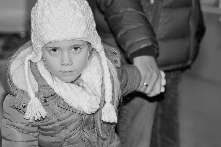 כללים להורות יעילה: ילדה מסתכלת על המצלמה כשאימה מחזיקה בידה מאחור