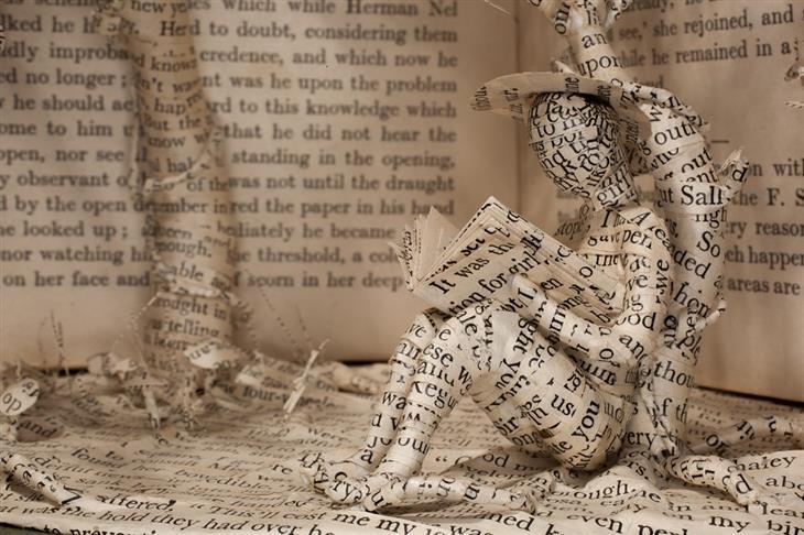 פסלים מנייר בתוך ספרים: מבט מקרוע על  דמות קוראת ספר מתחת לעצים