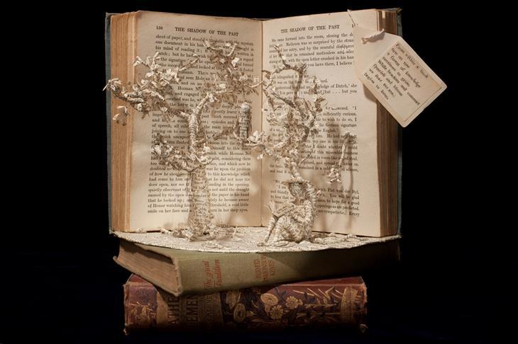 פסלים מנייר בתוך ספרים: דמות קוראת ספר מתחת לעצים
