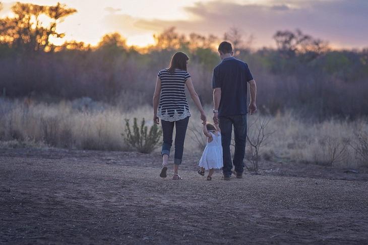עצות לגידול ילדים: הורים הולכים יד ביד עם ילדה