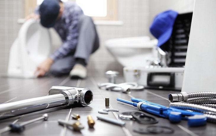 בדיקת צנרת לדירה: כלי אינסטלציה ואדם שמתקן כיור בחדר שירותים