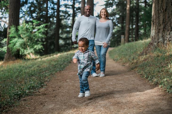 הורות מגדלור: ילד רץ לפני הוריו בשביל בחורשה