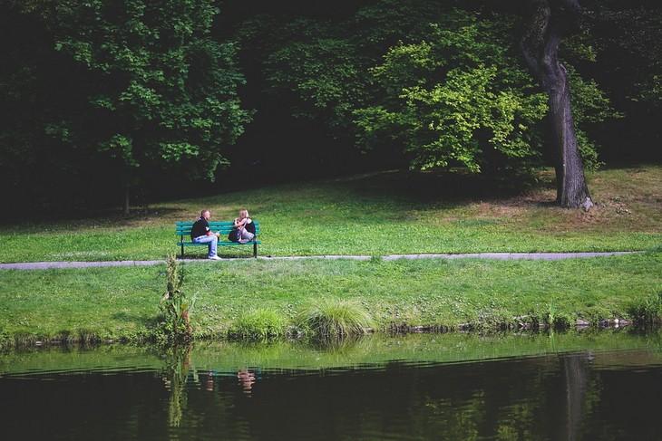 כללים להיות בני זוג נאמנים ותומכים: גבר ואישה יושבים פנים מול פנים על ספסל לצד אגם