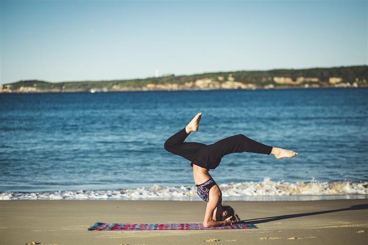 מדיטציה למוח צעיר יותר: איש עושה עמידת ראש בים