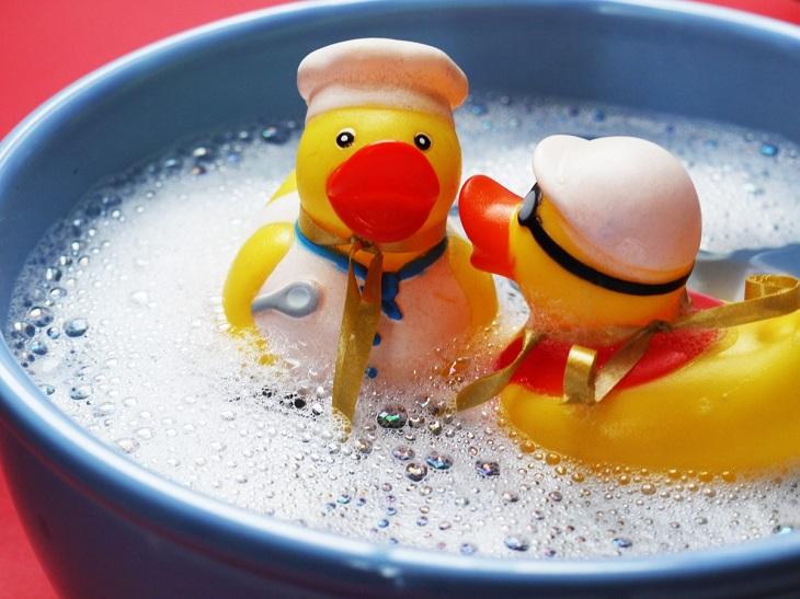 ניקוי חדרי ילדים: זוג ברווזי פלסטיק בתוך גיגית מים עם סבון