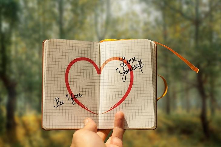"""התמודדות עם קשיים: יד אוחזת במחברת פתוחה שבתוכה איור לב וכתוב בה באנגלית """"אהיה עצמך, אהוב את עצמך"""""""