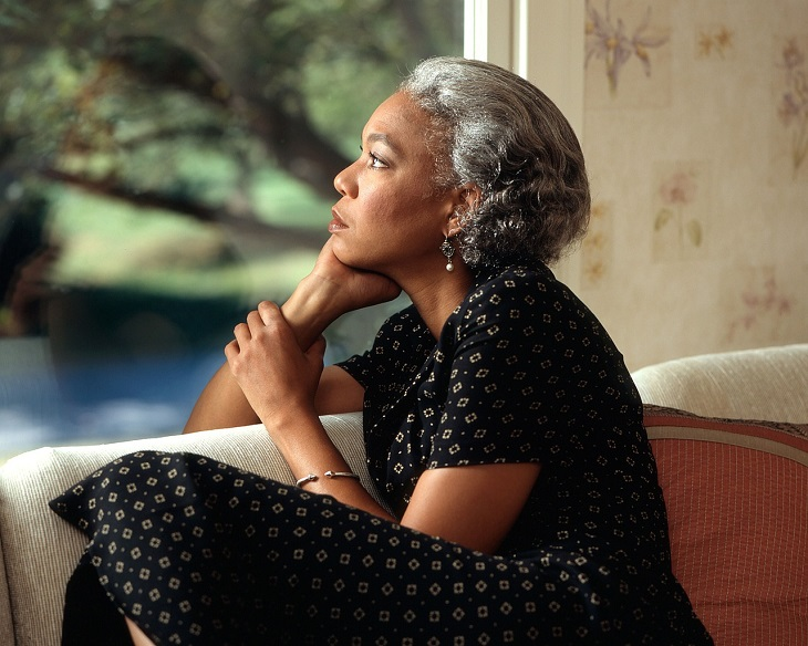 התמודדות עם קשיים: אישה יושבת בהבעת פנים רצינית, ידה מתחת לסנטרה והיא מסתכלת הצידה