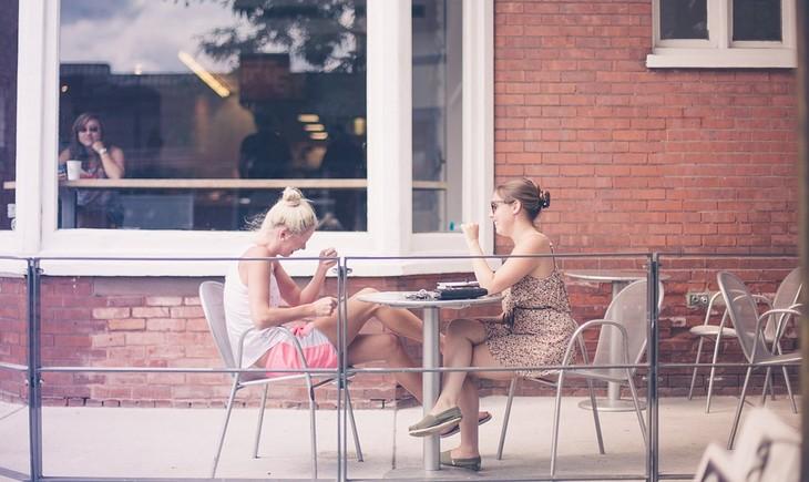 דברים שהזנחנו וצריך לחזור לעשותם: שתי חברות יושבות בבית קפה וצוחקות