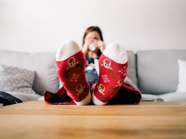 דברים שהזנחנו וצריך לחזור לעשותם: אישה יושבת עם רגליים על שולחן וכוס קפה ביד