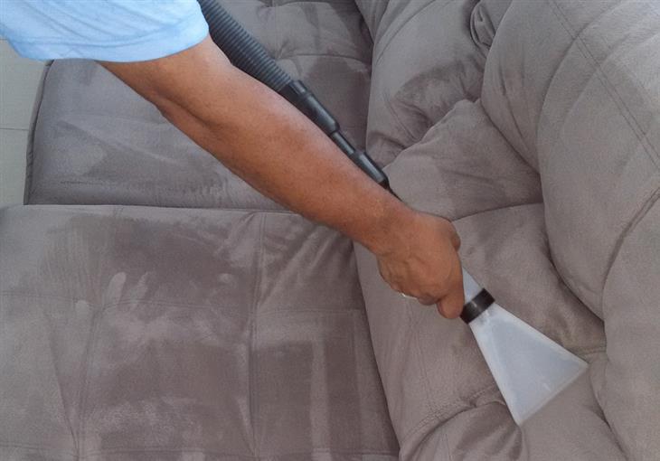 איך לנקות את הספה: איש מנקה ספה עם שואב אבק