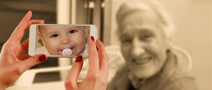 חידושים בתחום הרפואה: אישה מצלמת אישה מבוגרת בסמארטפון, ובמכשיר היא נראית כתינוקת