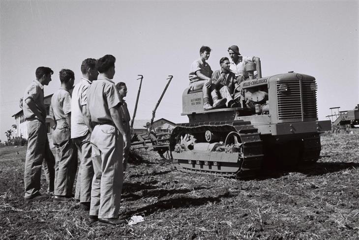 תמונות היסטוריות של ראשית ההתיישבות בארץ: סטודנטים לומדים כיצד לתפעל טרקטור שרשראות בזמן חריש
