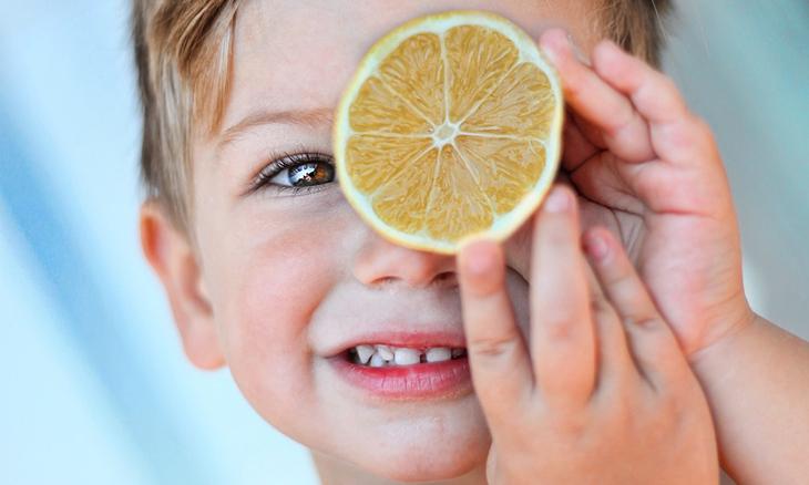 ויטמינים לילדים: ילד מחזיק חתיכת לימון מול עינו