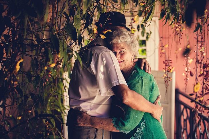 שינויים שזוגות צריכים לעשות: זוג מבוגר מתחבק בגינה, האישה מסתכלת על המצלמה