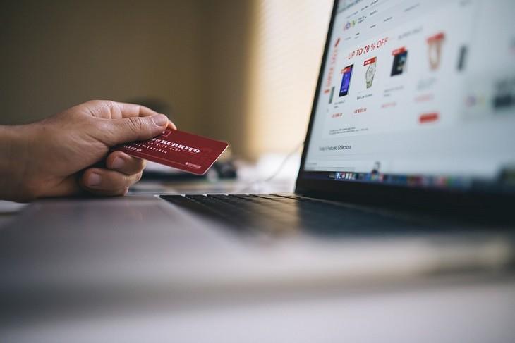 המטרדים הנפשיים שמובילים לבעיות כלכליות: יד מחזיקה כרטיס אשראי ליד מסך מחשב נייד