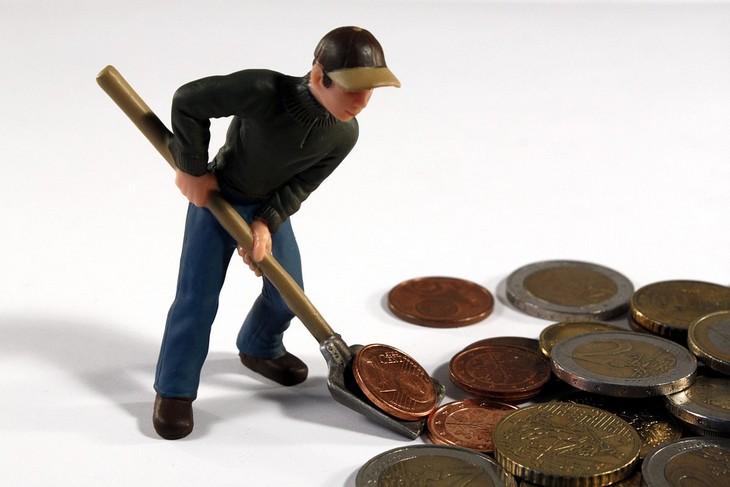 המטרדים הנפשיים שמובילים לבעיות כלכליות: בובה של גבר מעמיס באת חפירה מטבעות של יורו