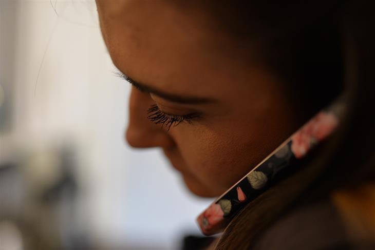 טעויות נפוצות שגורמות לכאבים: אישה מדברת בטלפון