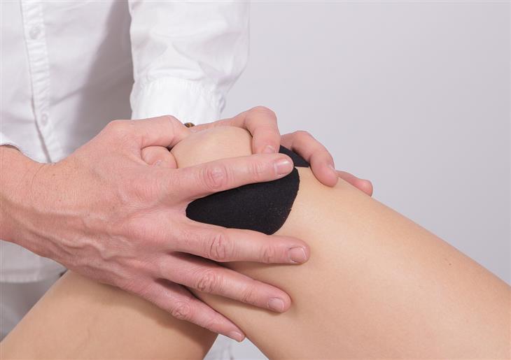 טעויות נפוצות שגורמות לכאבים: רופא מחזיק ברך של מטופל