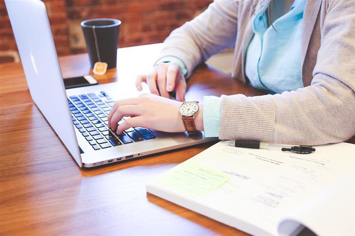 טעויות נפוצות שגורמות לכאבים: אישה יושבת מול מחשב נייד