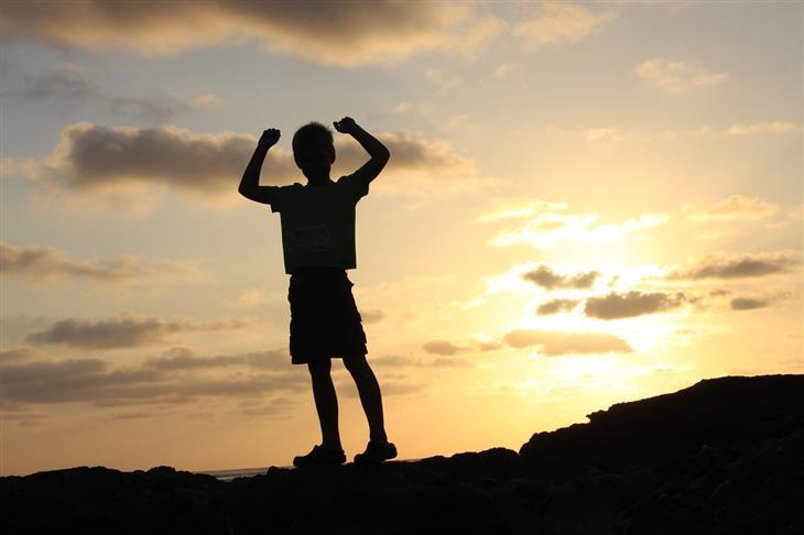 איך להגביר מוטיבציה להצלחה אצל ילדים: צללית של ילד מרים את ידיו מעלה