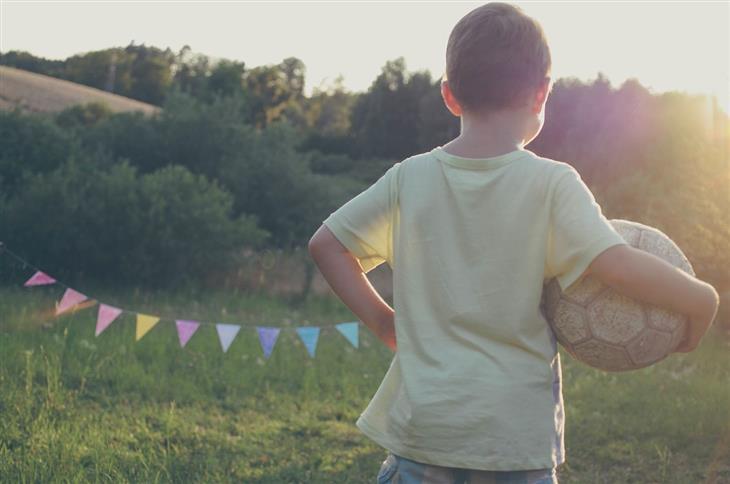 איך להגביר מוטיבציה להצלחה אצל ילדים: ילד מחזיק כדורגל