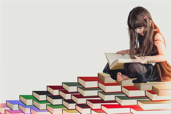 איך להגביר מוטיבציה להצלחה אצל ילדים: ילדה יושבת על ערימת ספרים וקוראת ספר