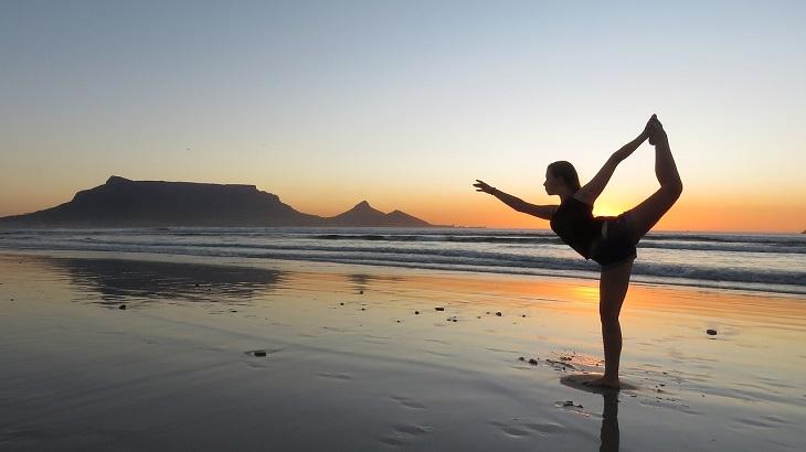 אטרקציות בדרום אפריקה: אישה מתאמנת על חוף הים על רקע הר השולחן