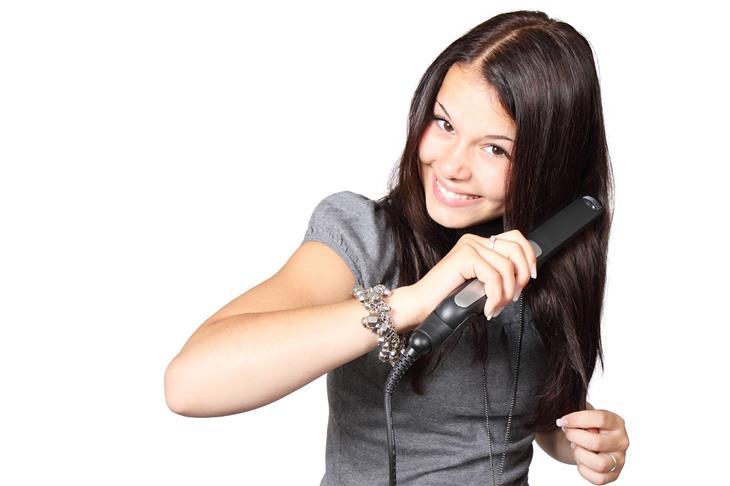 טעויות שגורמות לשיער שלכם להזדקן מהר: אישה משתמשת במחליק שיער על השיער שלה