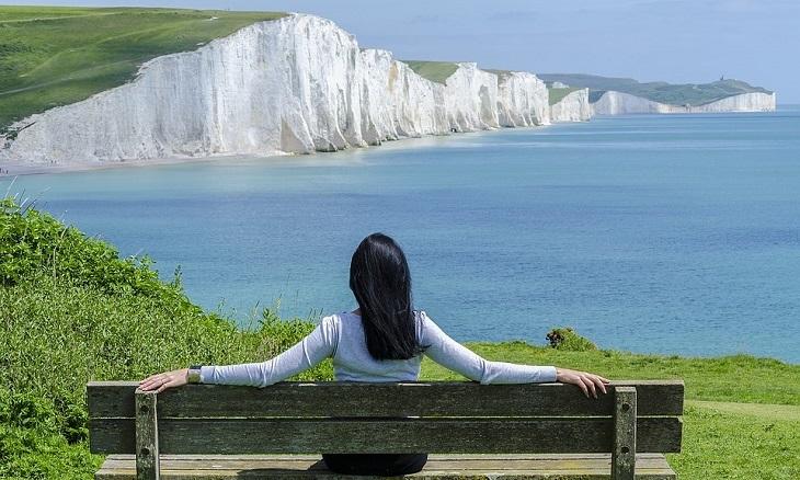 הרגלים מפתיעים לחיים מאושרים: אישה יושבת על ספסל מול נוף יפה של חוף ים
