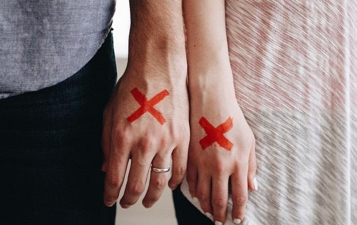 סימנים למניפולציות במערכות יחסים ומה ניתן לעשות: ידיים של גבר ואישה עם סימן X עליהן