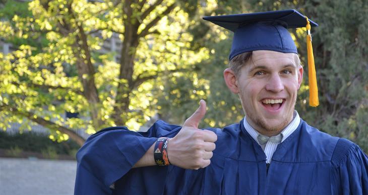 איך להיות מאושרים על פי קורס האושר של אוניברסיטת ייל: סטודנט שמח בבגדי סיום לימודים