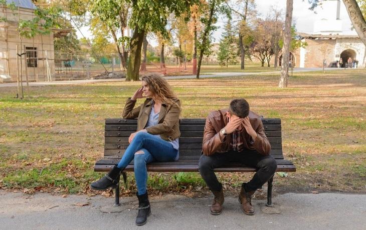 סימנים למניפולציות במערכות יחסים ומה ניתן לעשות: זוג יושב על ספסל כשהגבר מרכין ראש והאישה עם גבה אליו