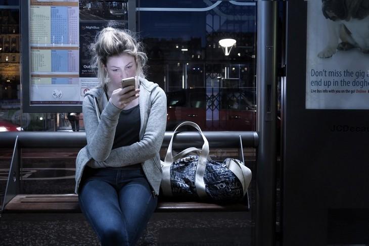 כיצד אסמסים משפיעים על הזוגיות: אישה יושבת בתחנת אוטובוס בחושך ובוהה בטלפון הנייד שלה