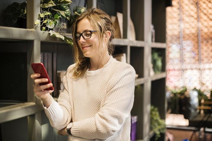 כיצד אסמסים משפיעים על הזוגיות: אישה מחייכת מחזיקה טלפון נייד בידה