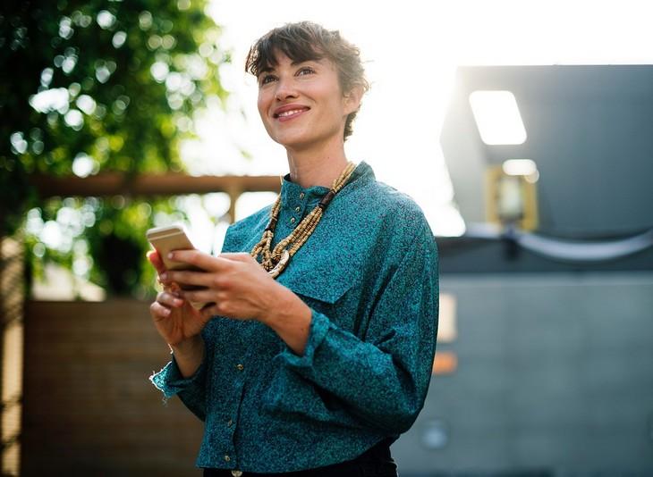 כיצד אסמסים משפיעים על הזוגיות: אישה מחייכת מחזיקה טלפון נייד
