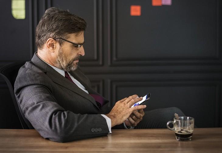 כיצד אסמסים משפיעים על הזוגיות: איש עסקים יושב לצד שולחן ומחזיק טלפון נייד בידיו