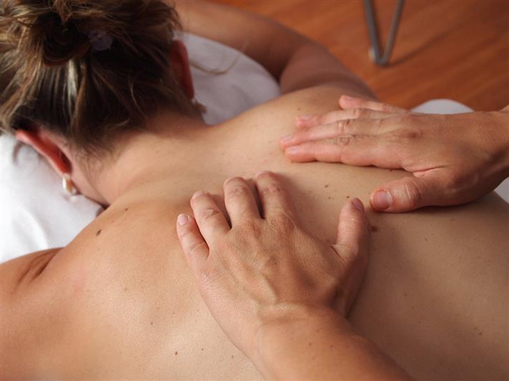 מדריך לעיסוי שוודי: ידיים של מעסה על גב של אישה