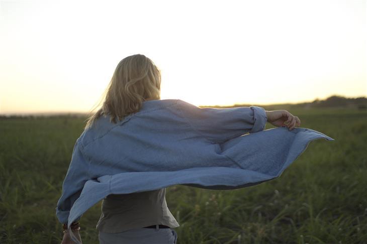 סימנים לדלקת חוליות מקשחת: אישה מרימה יד לצד בשדה