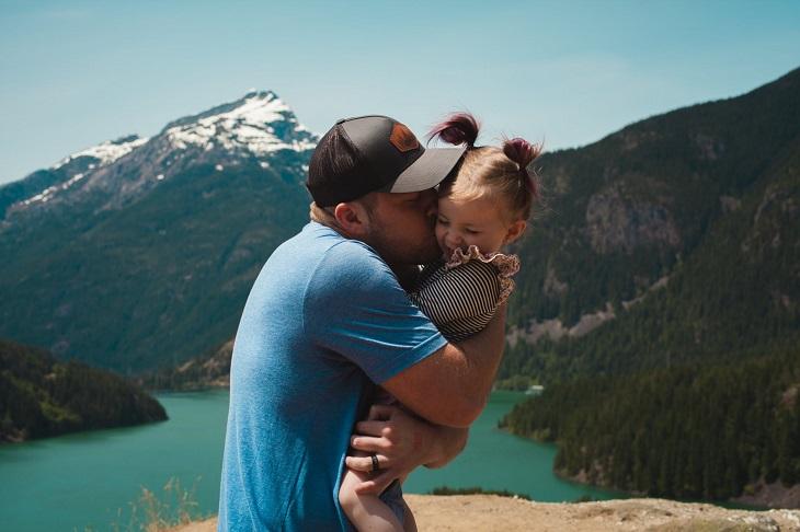 חיזוק קשר עם ילדים: אבא מנשק ילדה קטנה על רקע הרים ואגם