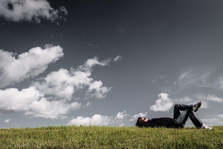 פעולות שצריך לעשות כדי להגיע לאושר: איש שוכב על דשא ומסתכל על השמיים