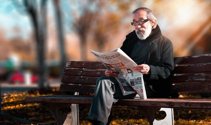 ברכה משעשעת לגיל 80: אדם מבוגר יושב על ספסל וקורא עיתון