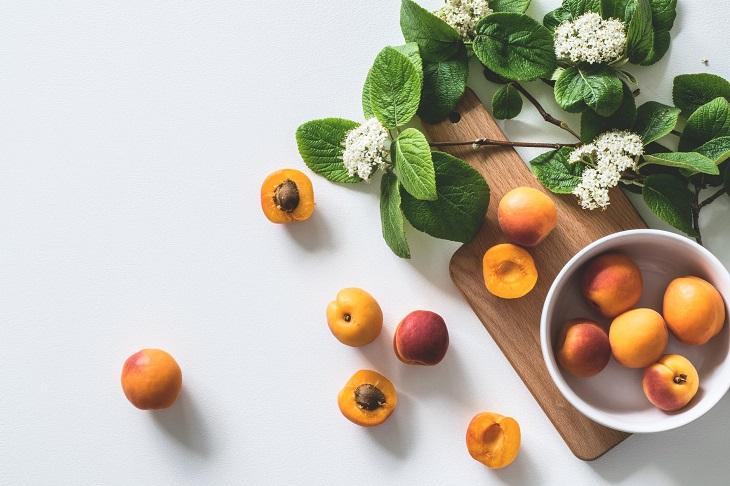 תועלות בריאותיות של משמשים: משמשים מפוזרים על שולחן ובתוך קערה, עם עלים ליד