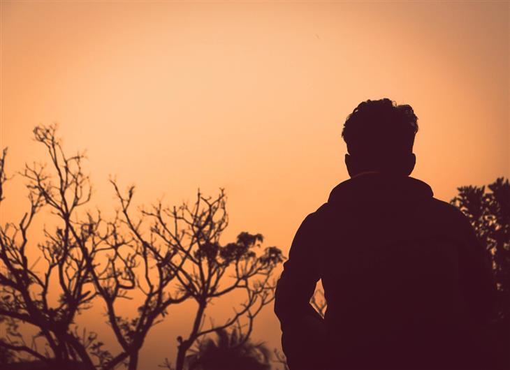 איך להתגבר על הפחד לאכזב אחרים: צללית של אדם יושב בטבע בשעת דמדומים