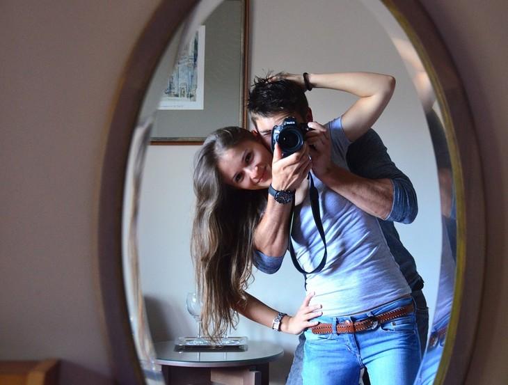 מה משפיע על איכות ה-WiFi: גבר ואישה מצטלמים מול מראה