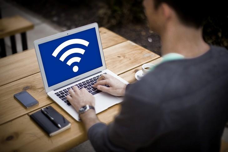 מה משפיע על איכות ה-WiFi: גבר יושב מול מחשב נייד