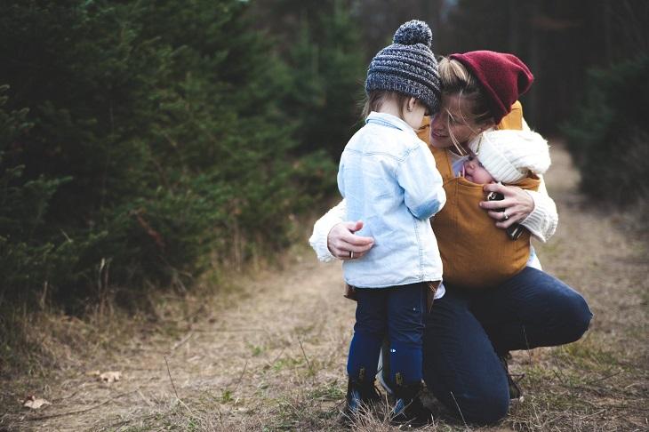 הורות חיובית: אמא, ילדה ותינוק בחורשה