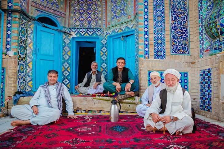 סדרת תמונות של אפגניסטן: חמישה גברים יושבים על שטיח