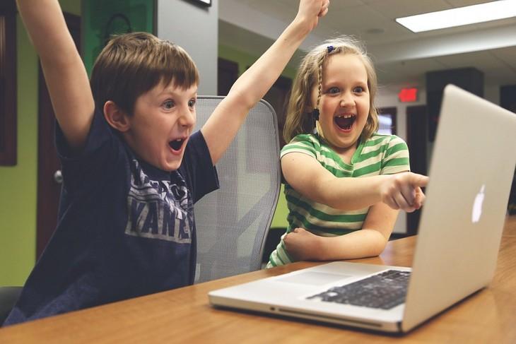 איך לגרום לילדים להפחית את זמני המסך: ילד וילדה מאושרים לנוכח מה שהם רואים במחשב נייד