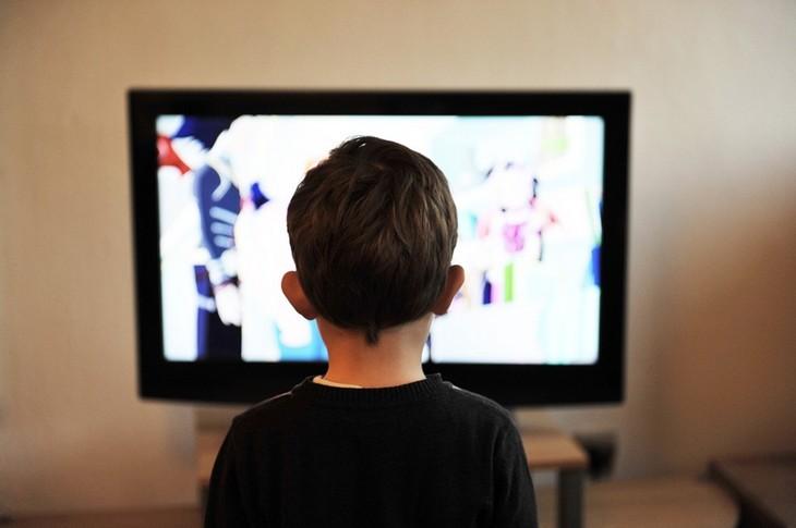 איך לגרום לילדים להפחית את זמני המסך: ילד עומד מול מסך טלוויזיה